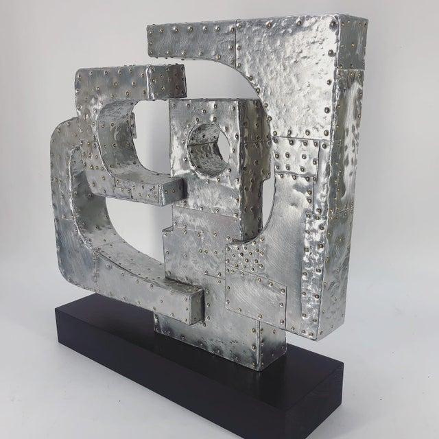 "Original work by American Artist Adam Henderson. Aluminum patchwork over wood, brass nails. Wood base. Measures 15"" tall x..."