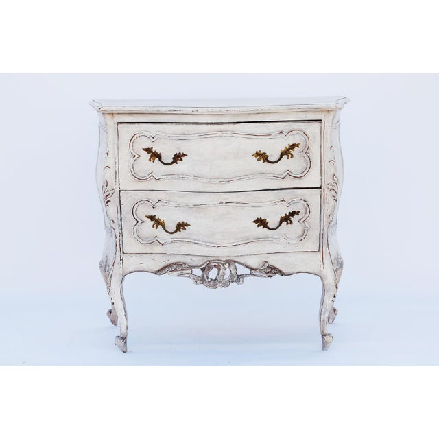 Pair of commodes, in the Rococo style, each with a painted finish showing natural wear, free-form molded top on raised and...