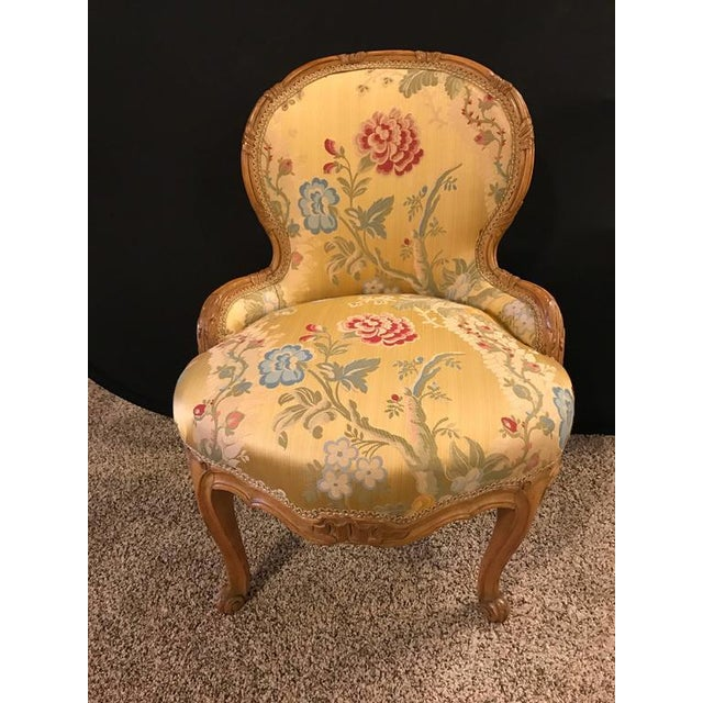 Louis XV Style Finely Carved Boudoir Chair With Two Tones Of Gold Leaf. Covered in a very fancy silk upholstery this early...