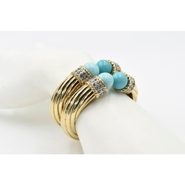 Stunning pair of bracelets featuring faux turquoise beads (2 shades on each bangle) with a 2 row of crystal color which...