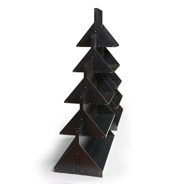 Uno sull'altro stacking double-sided bookcase of pyramid form,composed of graduated interlocking segments of painted wood...