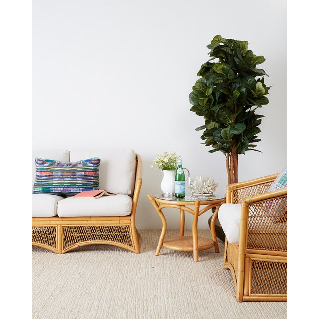 Sculptural Mid-Century Modern bamboo rattan and wicker settee or loveseat. Constructed from bent rattan with a waisted...