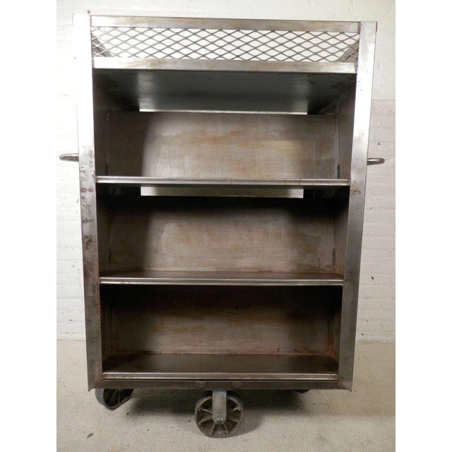 Heavy duty metal cart on over-sized casters. Once used in factories, can now be used as a rolling pantry or bookcase....