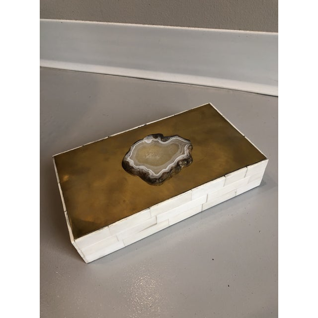 This Tozai Home box is covered in small rectangular pieces of bone along the sides with a brass metal reflective top. A...