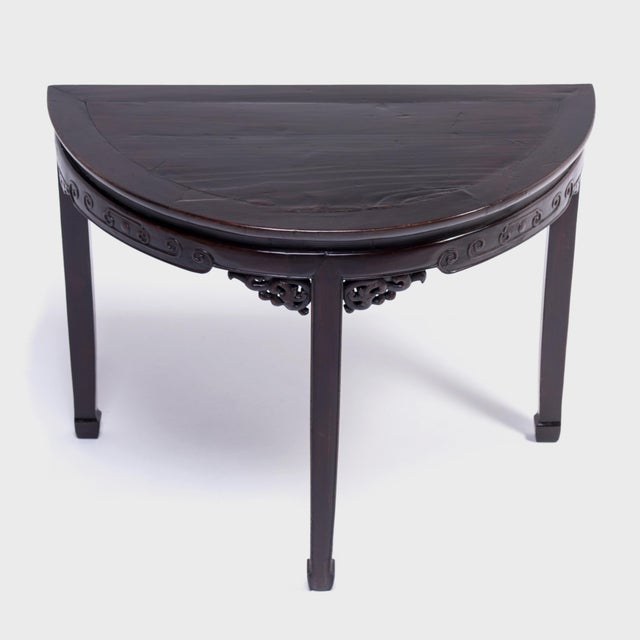 This demi-lune table is named for its half-moon shape was designed to sit against the wall of a Qing-dynasty home. Crafted...
