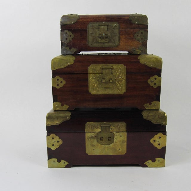 This trio of stacked Chinese jewelry boxes is hand-made from rosewood, brass, jade and silk-lined. The largest of the...