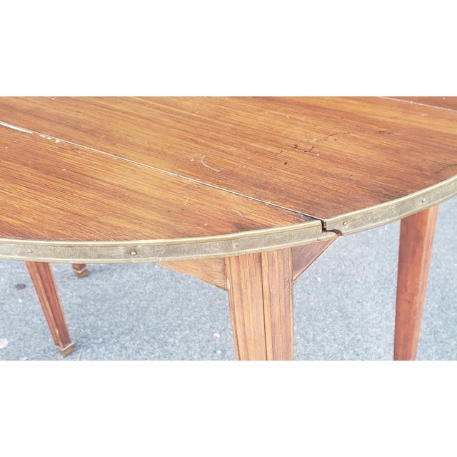 This is a very attractive mid century narrow mahogany Regency style drop leaf dining room table with 4 leaves. c1950....