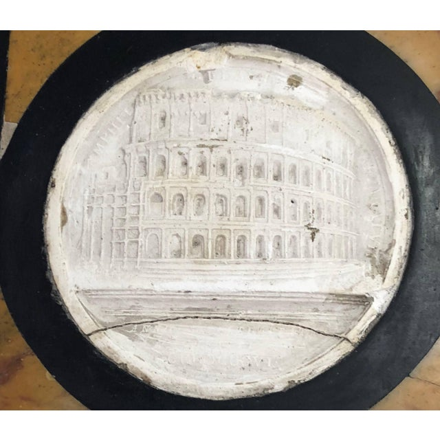 The paperweight inset with a plaster cast of the Coliseum, outlined in 'marmo nero' and marmo giallo.