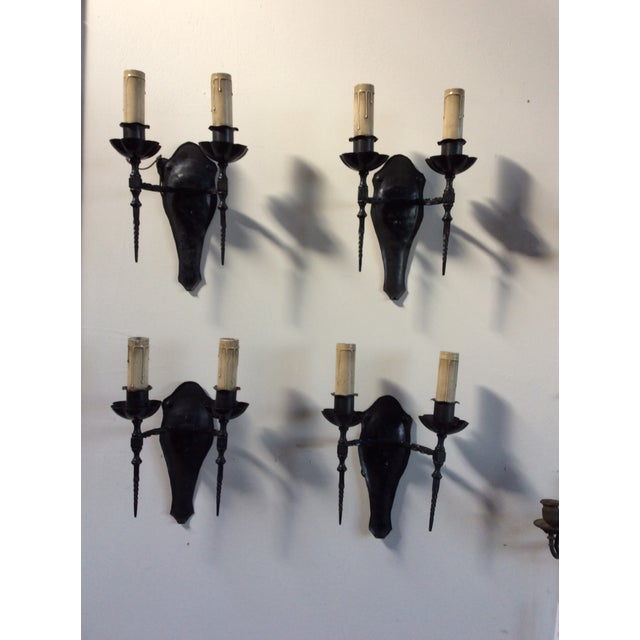 This is a set of four 1920s wall sconces with older candle covers and nice detailed metal work.