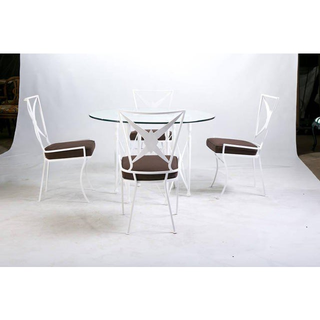 A Hollywood Regency dining set comprised of a round metal table with removable glass top and four chairs. Note the table's...