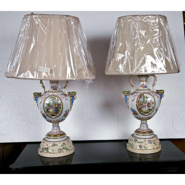Pair of paint decorated porcelain lamps. Possible Meissen. the fronts depicting a finely done genre scene, the reverse...