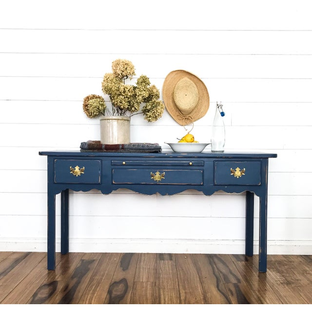 This lovely solid pine table has been hand painted in Ink Blue and professionally sealed for durability. The drawers are...