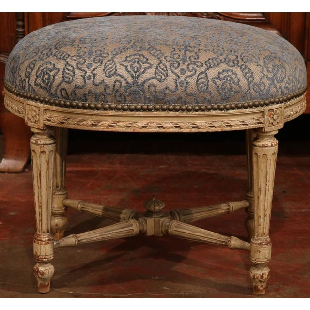 Elegant antique beige painted stool from France, circa 1860. Beautifully carved with rosettes, fluted legs, bottom...