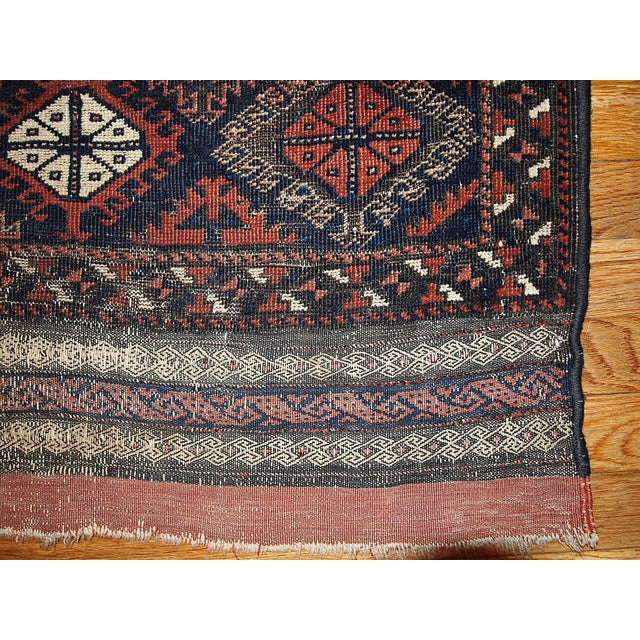 A handmade antique collectible Afghan Baluch rug in an unusual design. Tribal pattern in a deep burgundy color with a...