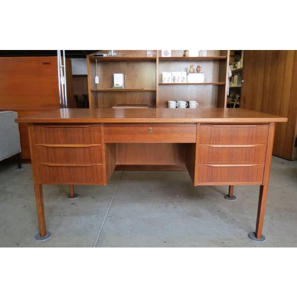 Vintage mid-cnetury modern teak desk. Features a generous sized work-top, seven smooth shallow drawers and a finished back...
