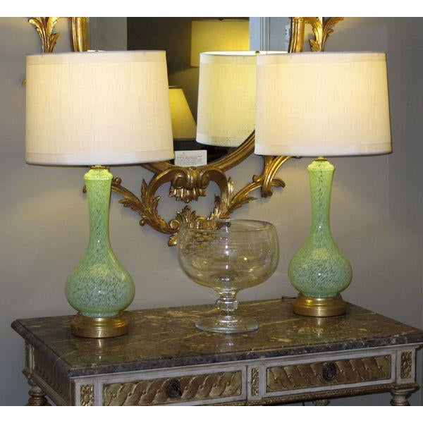 A shapely pair of Italian mid-century celadon-green bottle-form glass lamps; each bulbous form lamp of pale-green glass...