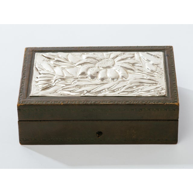 Italian tooled leather jewelry box with hand-wrought sliver repousse top. Hallmarked 920 on corner of silver top. Missing...