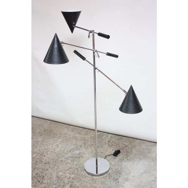 Striking three-fixture floor lamp manufactured by Lightolier in the 1950s. Composed of three conical, perforated shades in...