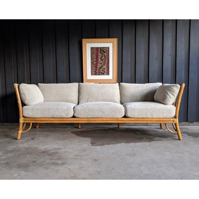 """Vintage McGuire of San Francisco """"cathedral back"""" bamboo/rattan sofa. Rattan construction with laced rawhide fastenings..."""