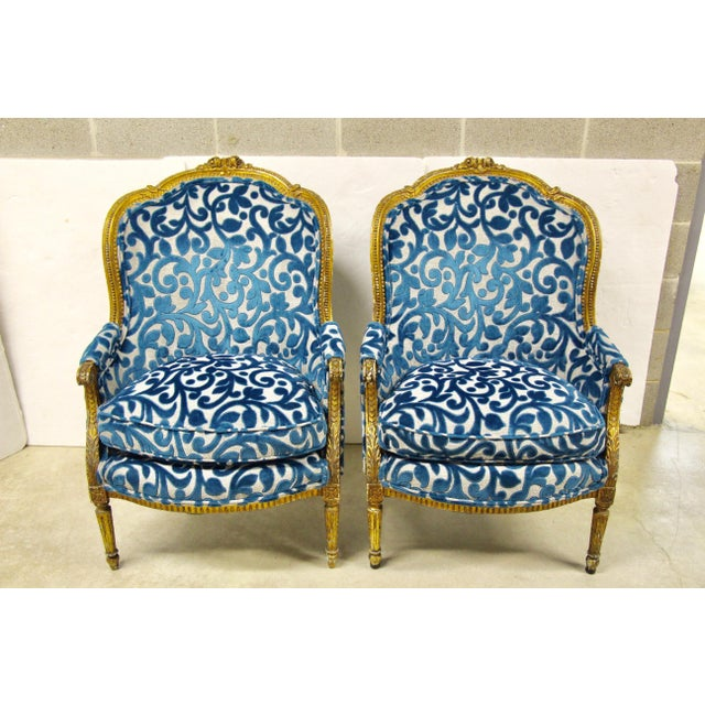 Remarkable pair of antique French giltwood bergere chairs. Newly upholstered in a Designer's Guild deep aqua cut velvet...
