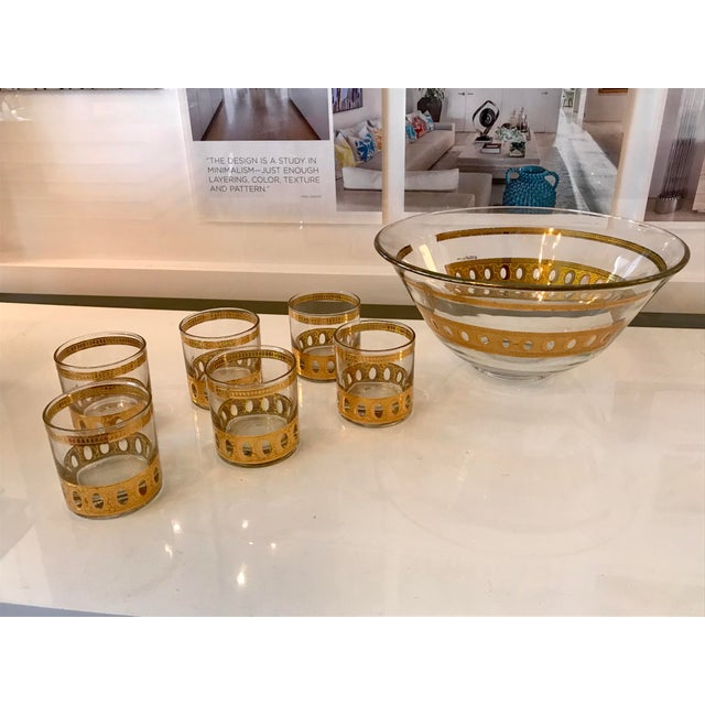 Great mid-century modern glass ice bucket or punch bowl with 6 matching glasses. Made by Culver Ltd. Glass Company, this...
