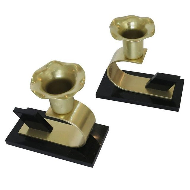 An elegant pair of polished brass and bakelite Art Deco Modernist floral candle holders designed by the Chase Metalworks...