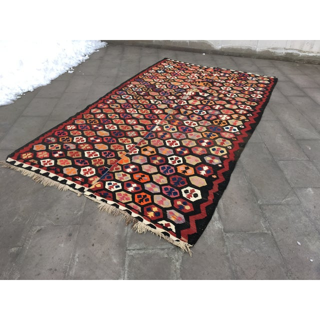 This is a Turkish kilim rug from the 1980s. The piece features a geometric pattern that symbolizes fertility.
