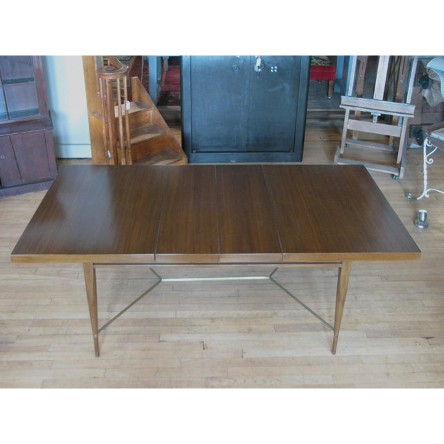 A very handsome vintage 1950s extension dining table in mahogany with brass stretcher by Paul McCobb for Calvin. Nice size...