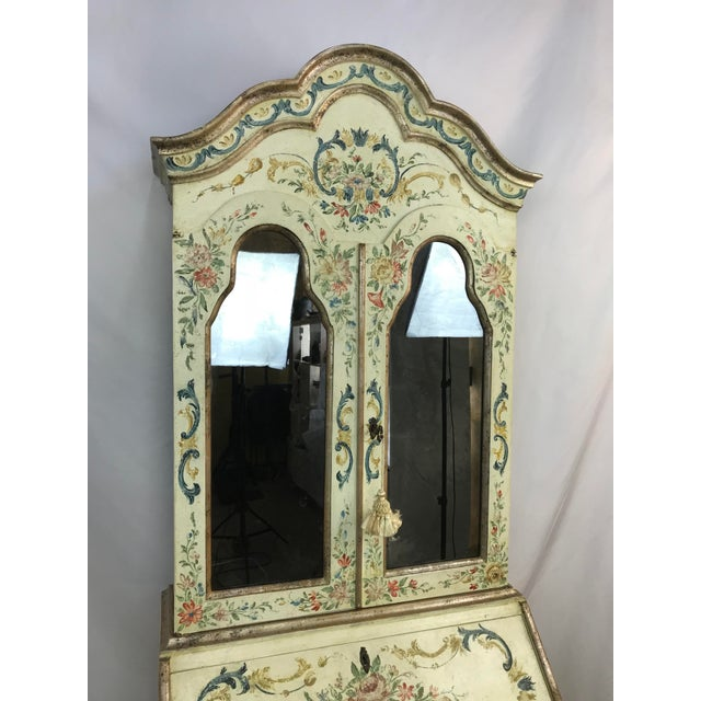 Cute Italian or cottage style antiqued rustic cabinet with cream colored paint and floral and geometric painted motifs. It...
