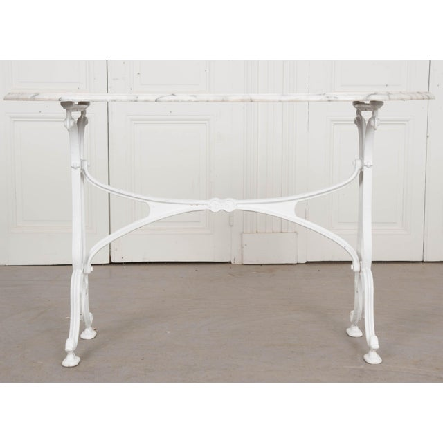 A classically styled French bistro table, made there just after the turn of the 20th century. The table features a white...