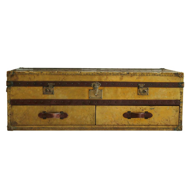 An English brass and leather campaign style coffee table. Leather straps and handles secured with brass nail heads give...