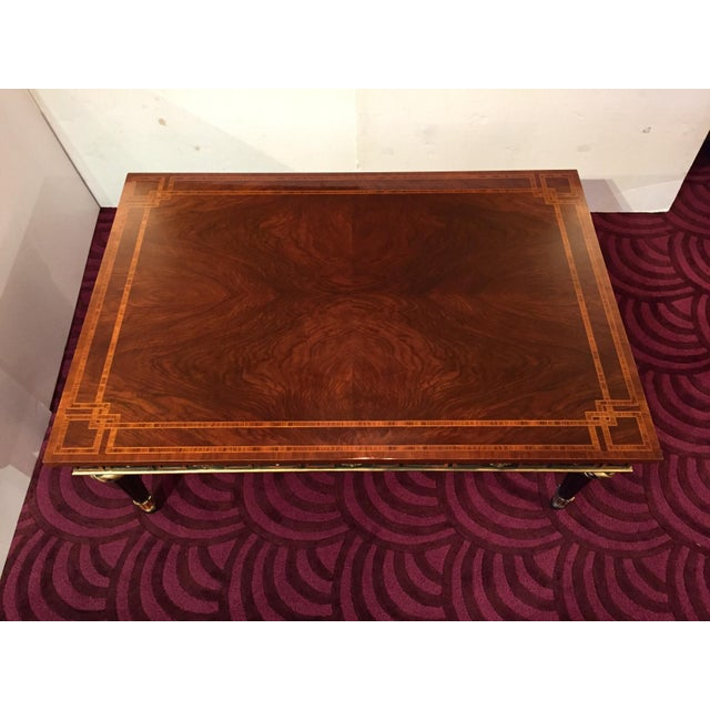 A sublimely rich Regency style book matched flame mahogany coffee table by John Widdicomb having magnificent satinwood...