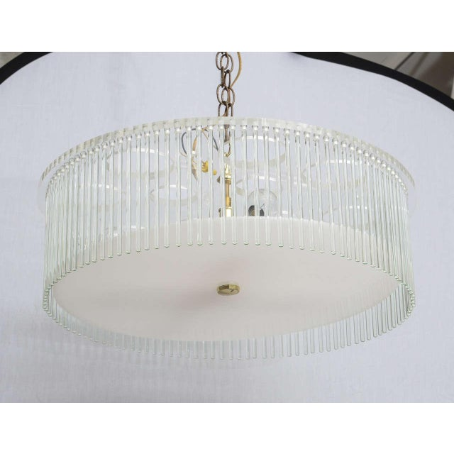 Lucite and glass chandelier. Two round discs of Lucite separated by an abundance of glass rods. Hold 4 clear light bulbs...