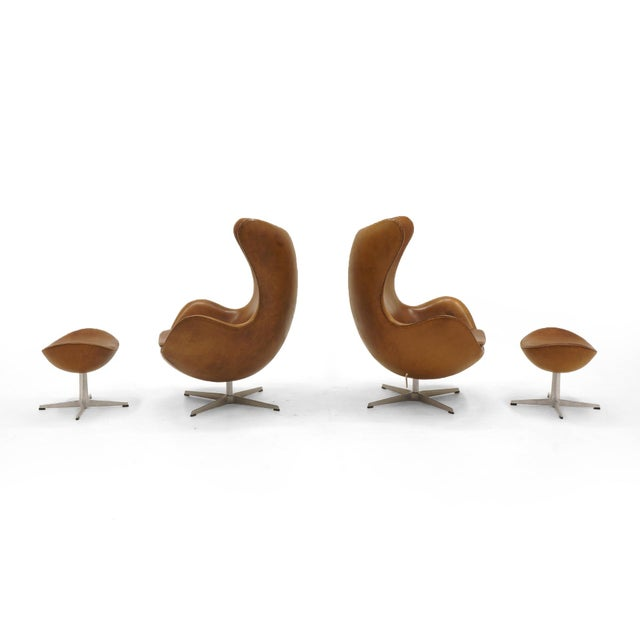 Pair of swivel tilt egg chairs and ottomans designed by Arne Jacobsen and manufactured by Fritz Hansen, Denmark....