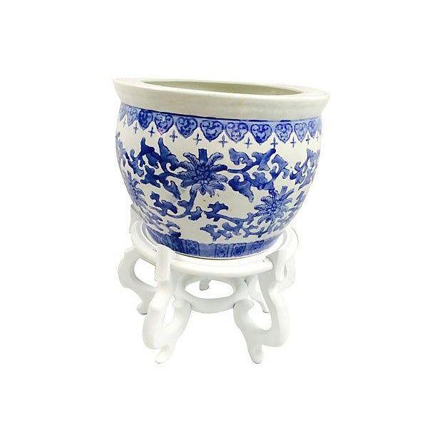 Blue-and-white porcelain Chinese botanical and Greek Key hand decorated planter with white painted wood stand. Made in China.