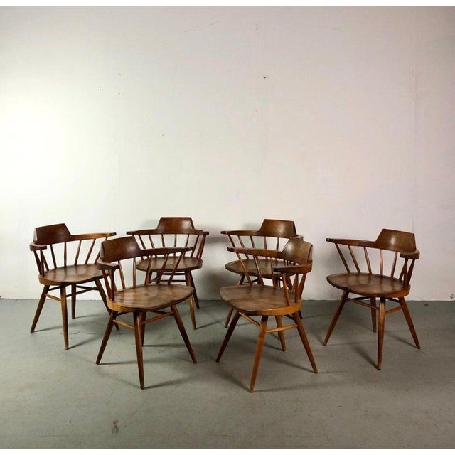 This set includes six early captain chairs and a one of a kind George Nakashima Plank dining table with two leaves. We...
