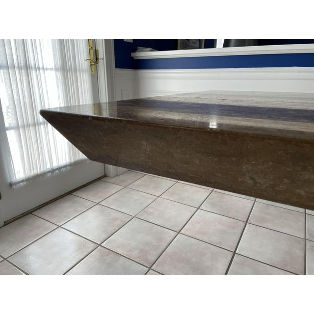 A beautiful, long contemporary natural stone dining table with a heavy rectangular top and boxed-shaped pedestal base. The...