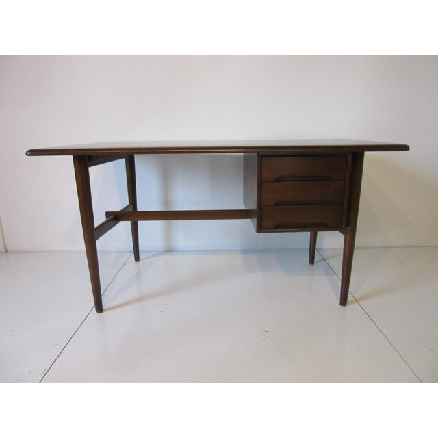 A nice smaller sized dark walnut toned desk with three drawers and a semi triangular top , cut out pulls and stretcher to...