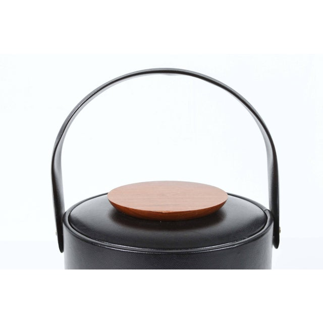 Vintage Georges Briard signed Mid-Century Modern black vinyl covered ice bucket. The cover features a teak wood button....