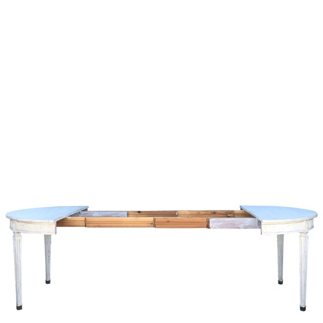 A Swedish Gustavian style, four-leaf extension dining table with tapered legs and brass feet, detailed carving on the...