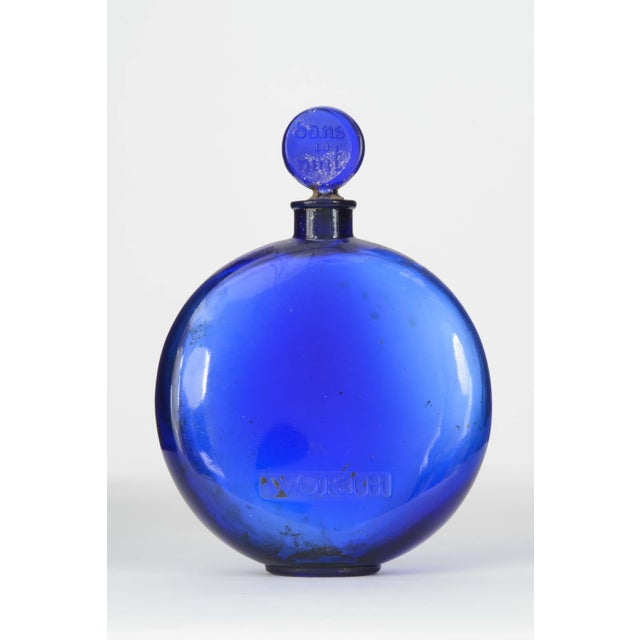"French Art Deco disc-shaped blue-tinted glass perfume bottle (DANS LA NUIT by WORTH) with brand name ""Worth"" engraved on..."