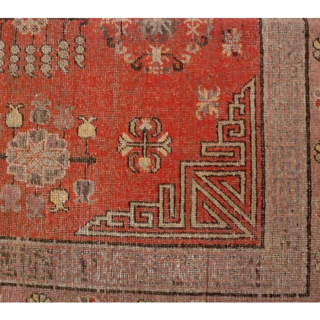 A late 19th century Central Asian Khotan rug with all-over floral pattern on a crimson background, surrounded by multiple...