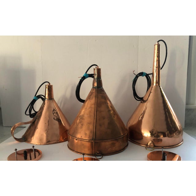 A trio of varied antique copper funnels cleverly electrified ad transformed into light pendants. Each fixture takes a 60...