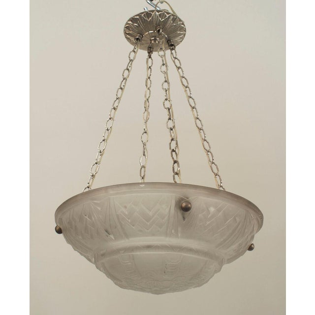 French Art Deco (circa 1925) round pendant form frosted glass bowl form chandeliers with a geometric border and floral...