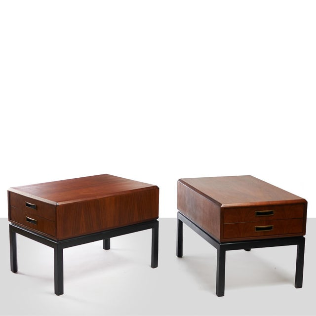 A pair of two toned walnut night stands in the style of Harvey Probber. The pair feature ebonized legs, eased edges, and...