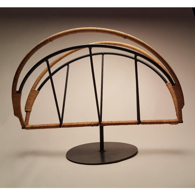 Open and elegant, this black iron and rattan magazine rack is functional, yet sculptural. Designed by Arthur Umanoff for...