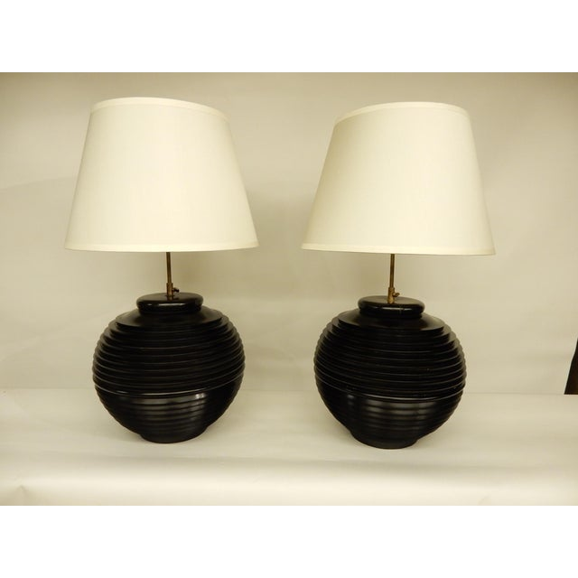 Pair of French Mid-Century Modern table lamps with brass adjustable necks. The lamps are made of wood and painted. Height...