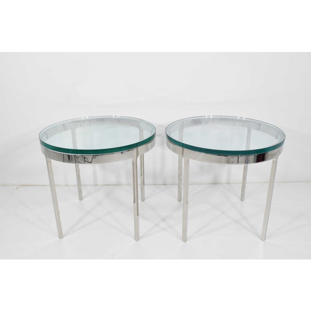 """A pair of side tables by Nicos Zographos in polished stainless steel with a 3/4"""" polished glass top."""