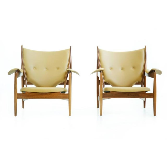 Finn Juhl for Baker, pair of Chieftains. Upholstered with Spinneybeck leather hides, walnut frames. Applied metal tags...