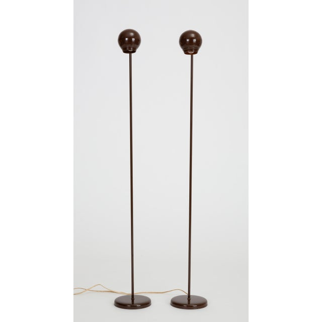 A delicate floor lamp with a glossy brown enamel finish provides concentrated task lighting via a rounded ball shade with...
